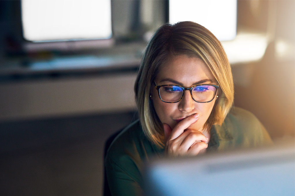 woman looking thoughtfully at a computer