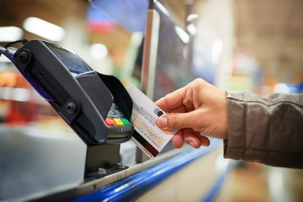 person using a credit card at a supermarket check-out