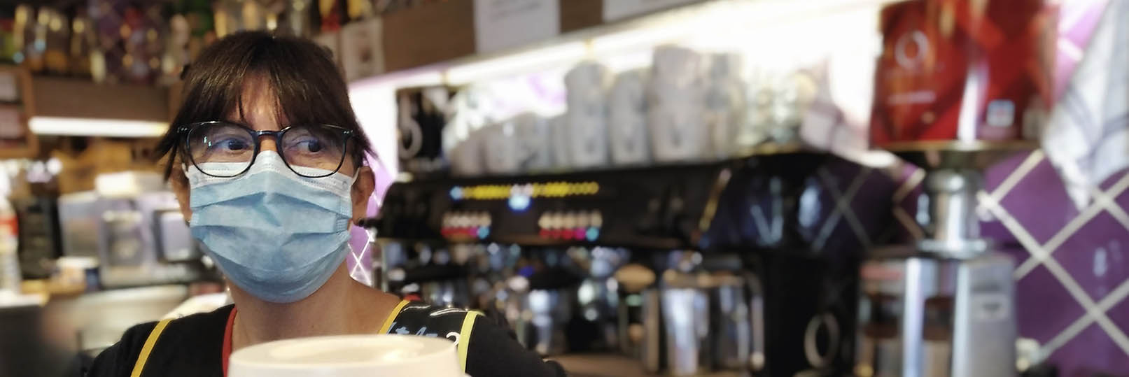 barista in a cafe behind the counter wearing a mask